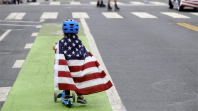 Child on a scooter wearing an American flag as a cape