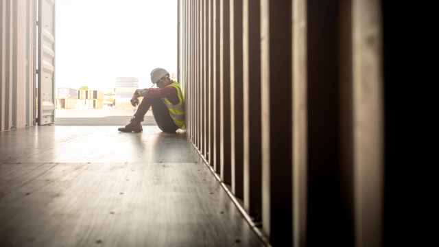 Sad-looking worker in a hard hat and reflector vest sits in a container box at a shipyard
