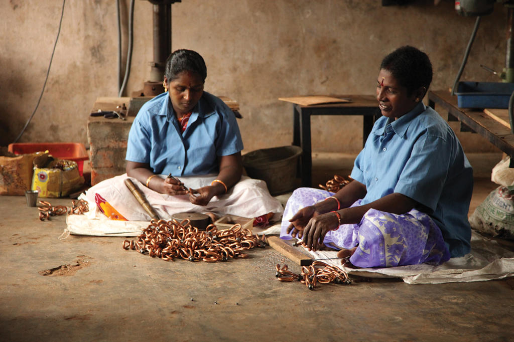 Women at an extraction plant in Hyderabad, India, work with copper chains to create Servals' clean-energy products.