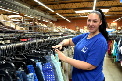 A worker at Goodwill Industries of San Diego County – a San Diego Workforce Partnership partner and subject of a Reimagine Retail publication – sorts clothing.