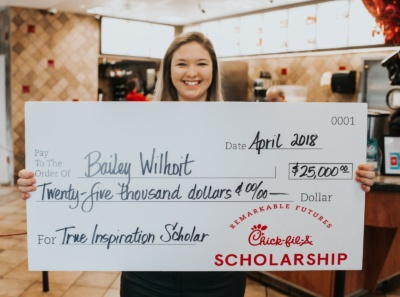Chick-fil-A employee holding a giant scholarship check.