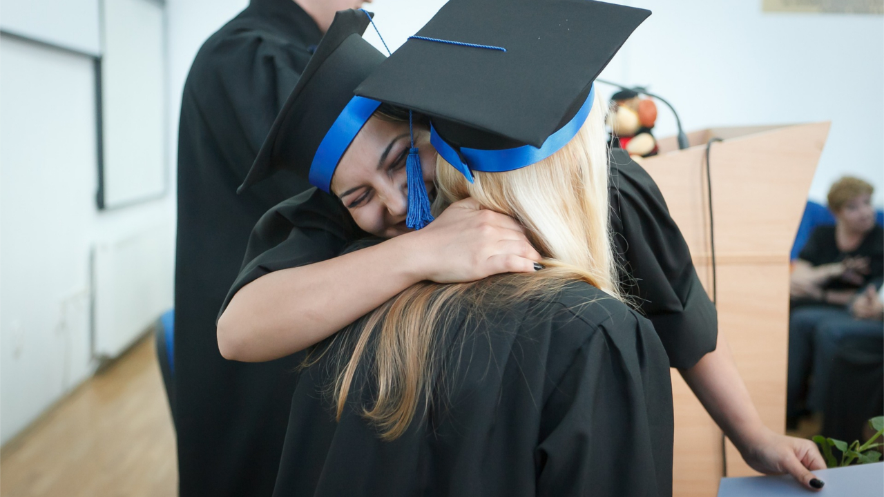 Women in graduation attire hugging during commencement.
