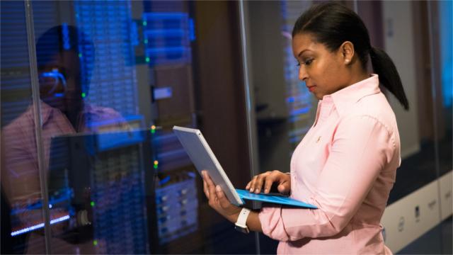 Woman Wearing Pink Dress Shirt Holding Gray Laptop Computer