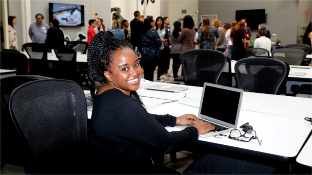 2018 CODE: Rosie participant Angela Alexander sitting in front of a laptop.