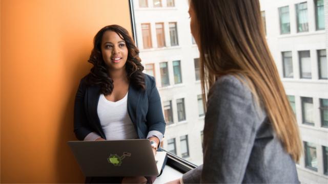 Woman Wearing Gray Blazer Facing Woman Wearing White Shirt and Black Blazer With Laptop on Lap