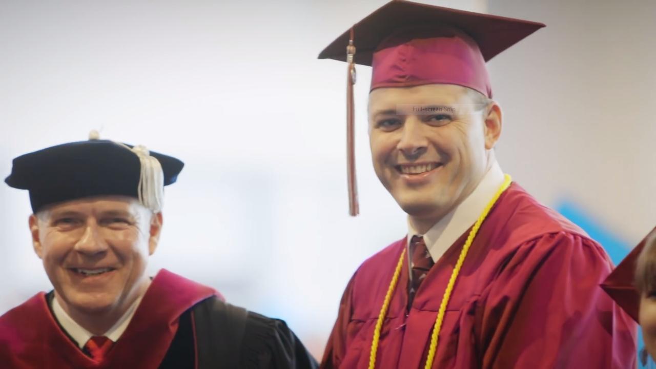 Student and professor in graduation attire