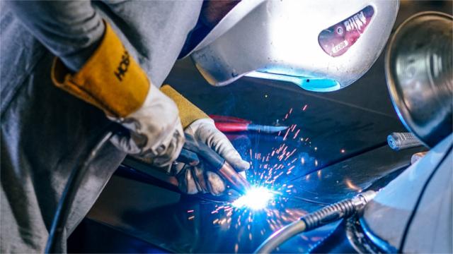 Auto worker welding a car