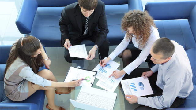 Top view of working business group sitting at a table during a corporate meeting