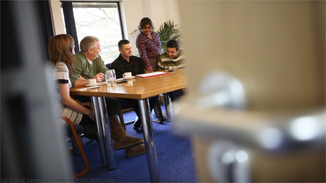 View through a partially opened door of a group of adults in a conference room
