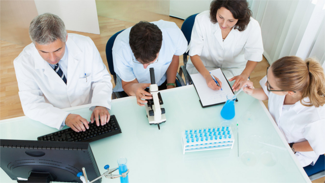 Four medical personnel working at a table together