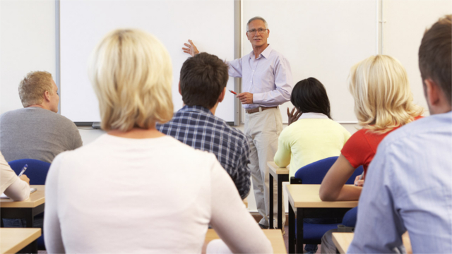 Teacher lecturing to a college classroom full of students