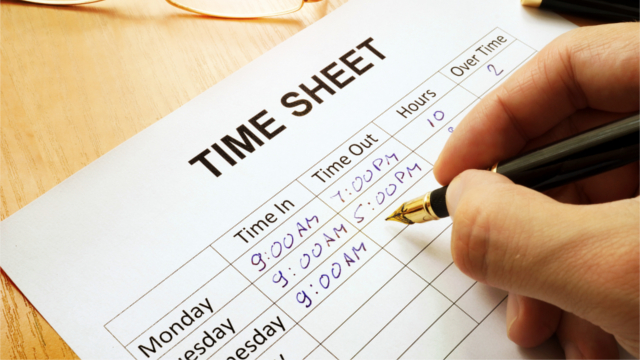 Employee writes hours on a time sheet