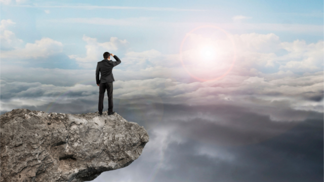 Man standing on a mountain, staring toward another mountain