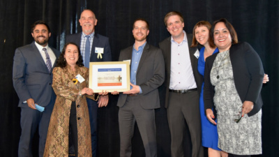 Representatives from LendingClub, Opportunity Fund, CAMEO, CDC Small Business, and Small Business Majority on stage to collect a Community Heroes award from California Reinvestment Coalition. Left to right: Gabrielle Villareal of Opportunity Fund, Heidi Pickman of CAMEO, Kurt Chilcott of CDC Small Business, Louis Caditz-Peck of LendingClub, Brian Pifer of Small Business Majority, Gwendy Brown of Opportunity Fund, Paulina Gonzalez of California Reinvestment Coalition.