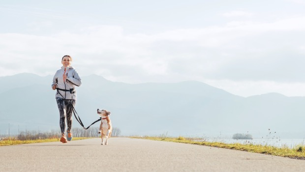 A woman running outside on a road with her dog.