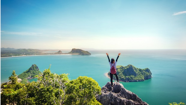 A woman standing on top of a mountain overlooking water with her arms raised.