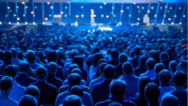 An audience listening to a speaker on stage.
