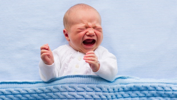 A baby crying on a hospital blanket.