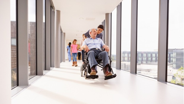 A nurse pushing a senior patient in down a hallway in a wheelchair.