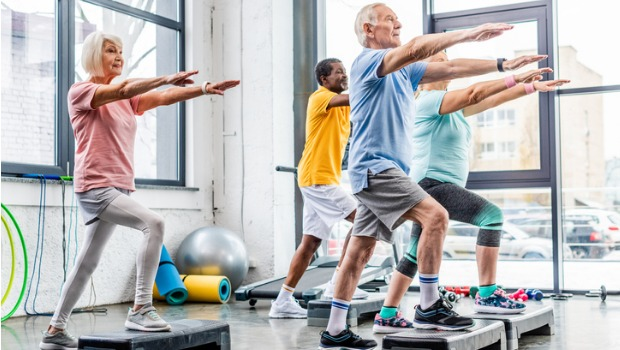 A group of seniors exercising on step platforms in a gym.