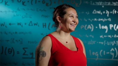 A woman in a red sleeveless top stands in from of a wall of mathematical equations. Photo credit: Jordan Stead / Amazon.