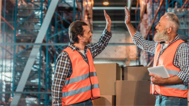 Two warehouse workers give each other a high five.