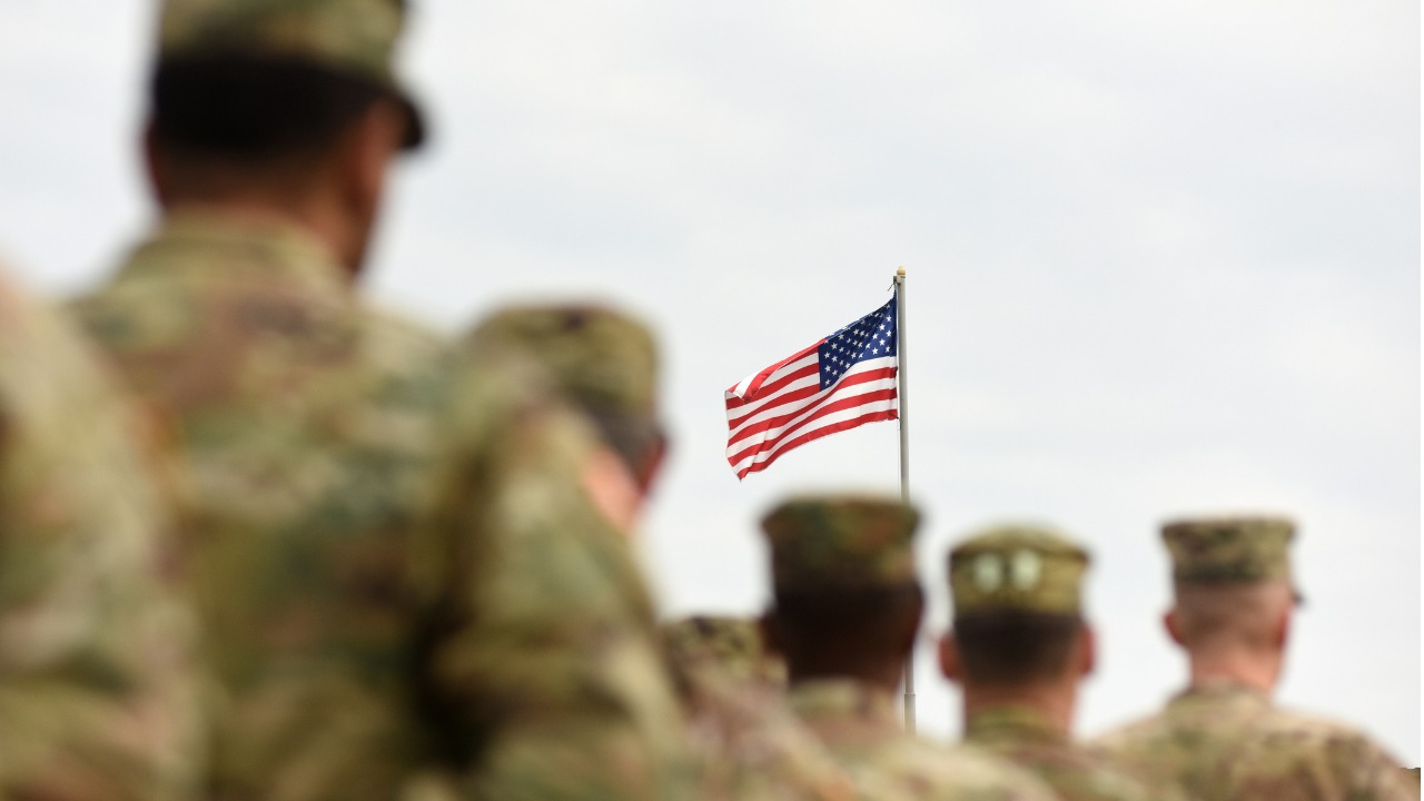 American soldiers with US flag in background.