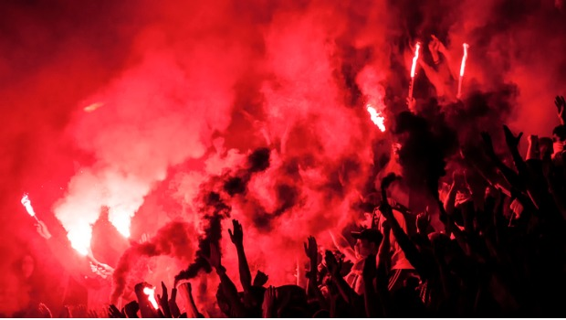 A crowd holding up red flares.