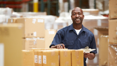 African American man working in warehouse, preparing goods for shipment