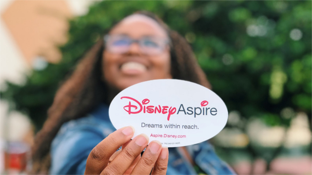 Disney employee holds up a sticker that says