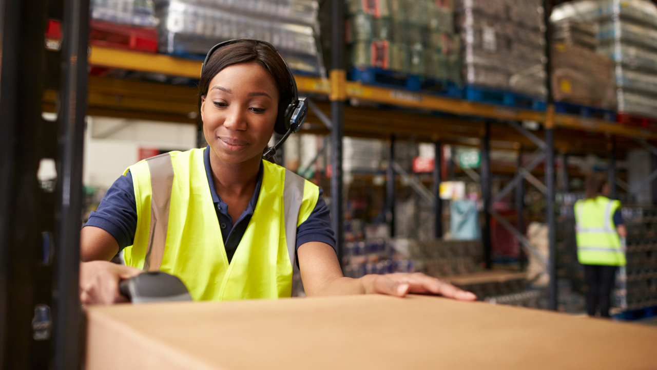 African American woman scanning boxes in a warehouse