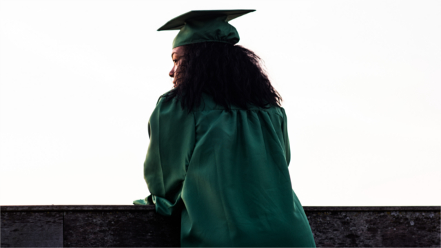 Woman in graduation cap and gown staring into the distance