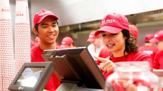 Two Five Guys employees work at the cash register