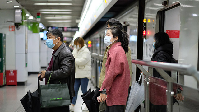 People wearing surgical mask walking out from subway in Shanghai