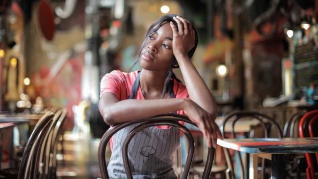 Restaurant worker sits in an empty restaurant, looking sad.