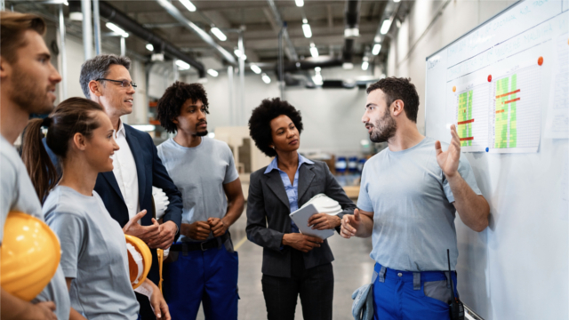 A factory worker presents a new business strategy to his managers and colleagues.