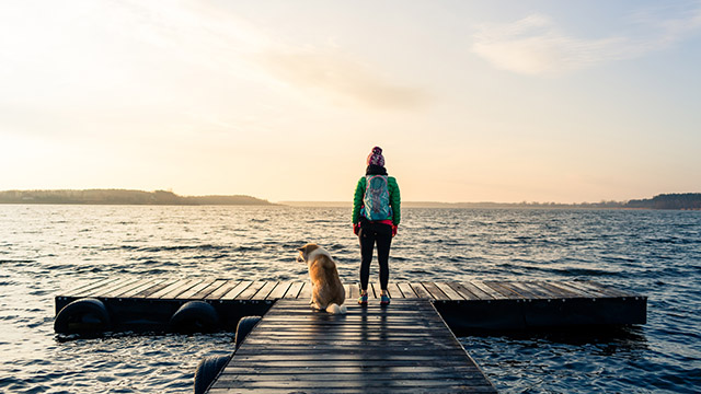 Woman with dog by ocean