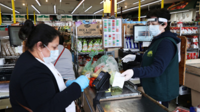 Grocery store worker and customer wearing masks in the checkout line (Photo courtesy of Marketplace. Credit: Al Bello/Getty Images)