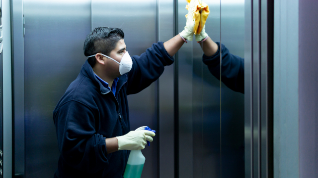 Hispanic man in a face mask cleaning the inside of an elevator