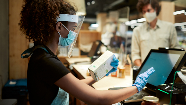 Photo of a young woman of color working at the checkout lane in a grocery store, wearing personal protective equipment, including a face mask, face shield, and gloves