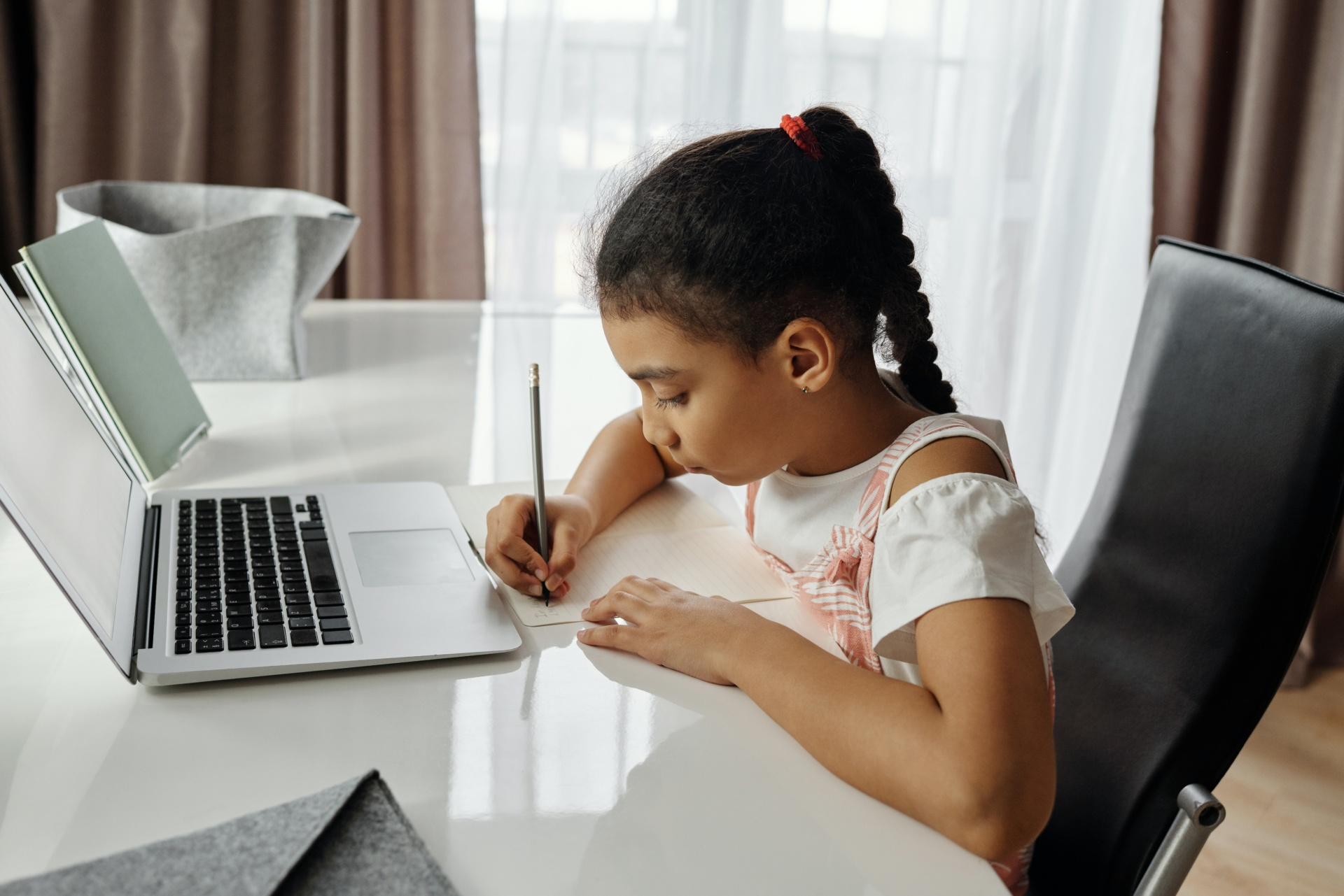 Little girl doing homework in front of laptop