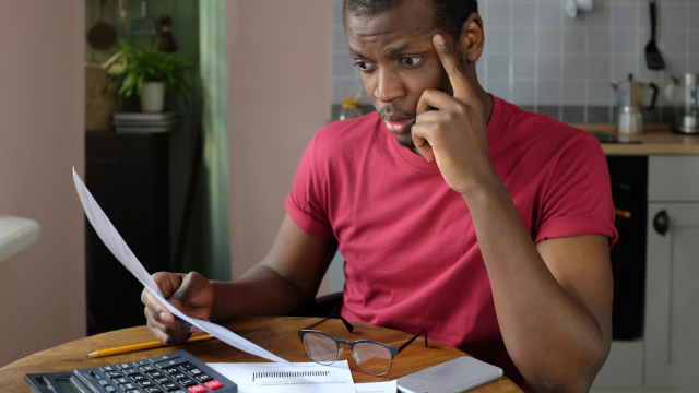 Photo of a concerned Black business owner staring at financial documents in front of a laptop, with glasses and calculator nearby