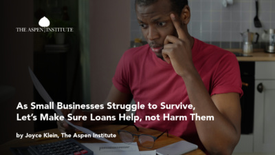 """Foreground: """"As Small Businesses Struggle to Survive, Let's Make Sure Loans Help, not Harm Them by Joyce Klein, The Aspen Institute."""" Background: Photo of a concerned Black business owner staring at financial documents in front of a laptop, with glasses and calculator nearby."""