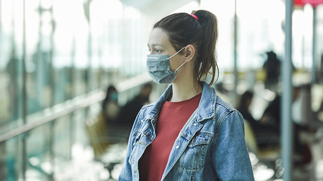 Woman wearing protective mask in airport