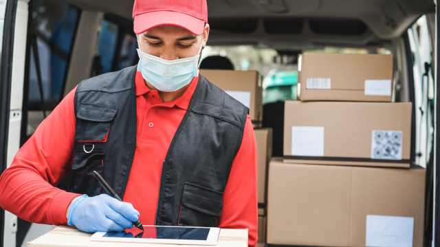 Photo of a delivery worker wearing a face mask and gloves