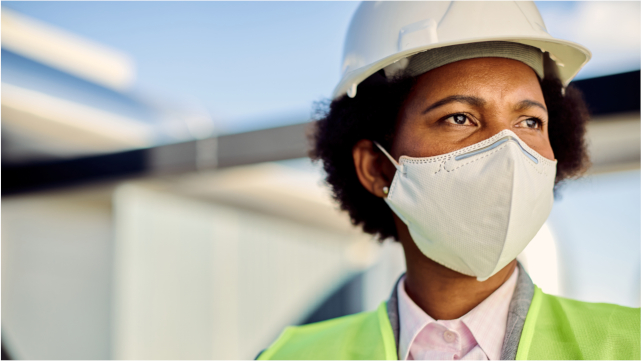 Black woman worker wearing a hard hat, reflector vest, and face mask.