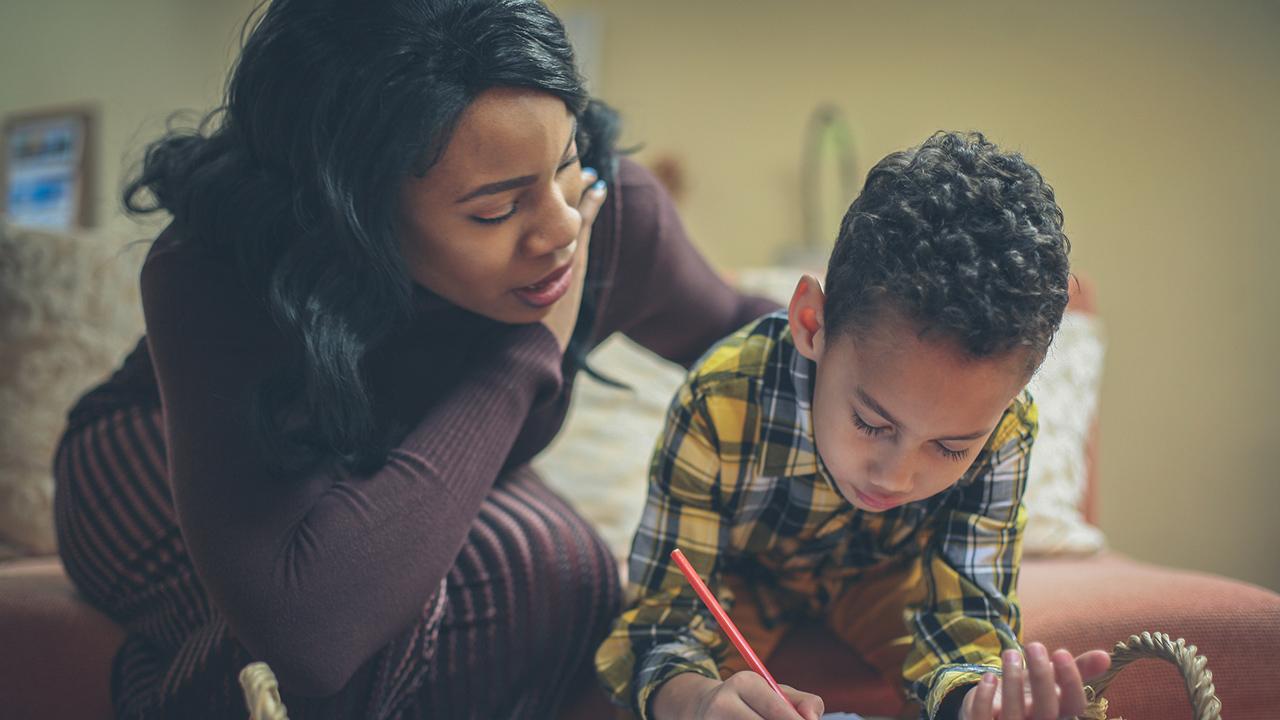 Preschool boy with his mother doing homework