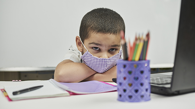 Sad school child with mask