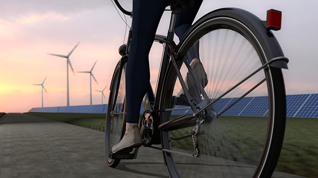 woman on bike in front of windmills