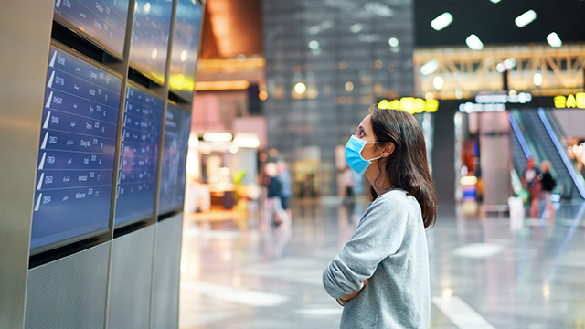 Woman with mask looking at departure board
